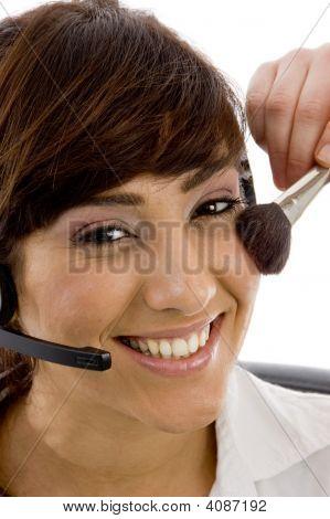 Close Up Of Smiling Female Customer Care Executive Applying Blusher