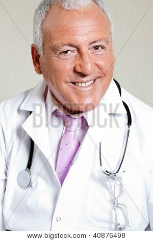 Portrait of senior male doctor smiling against colored background