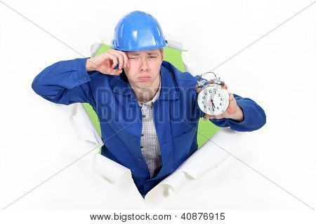 Bleary eyed construction worker with an alarm clock