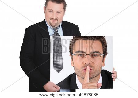 moon-faced man wearing coat and tie showing picture of young man with finger in mouth