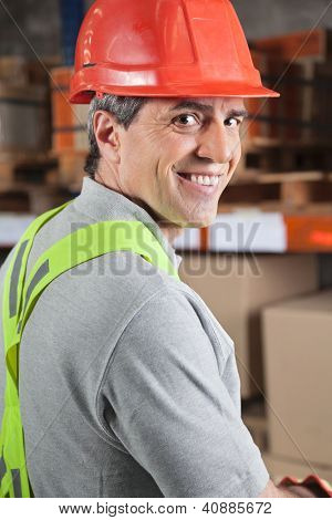 Portrait of happy mid adult foreman at warehouse