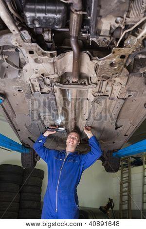 Portrait of confident male mechanic working under car