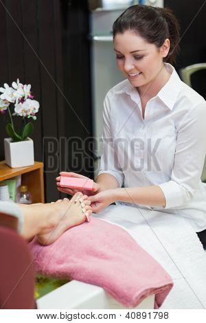 Young woman buffering toe nails at spa center