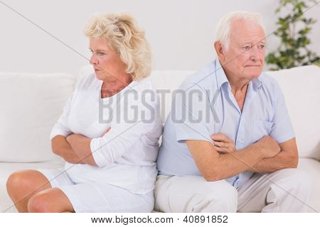 Unhappy woman being angry against an old man on the sofa