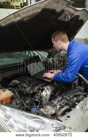 Male mechanic using laptop while repairing car engine