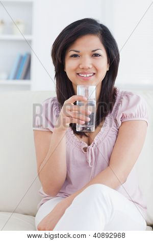Woman smiling while sitting on a couch and holding a glass of water in a living room