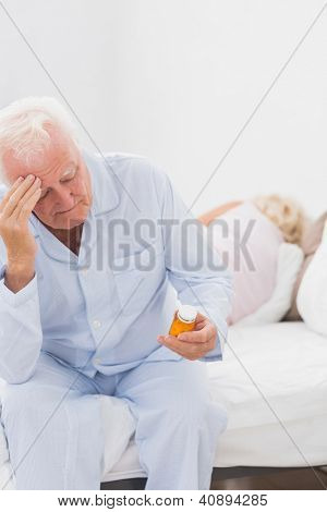 Old man holding pills while woman sleeping on the bed