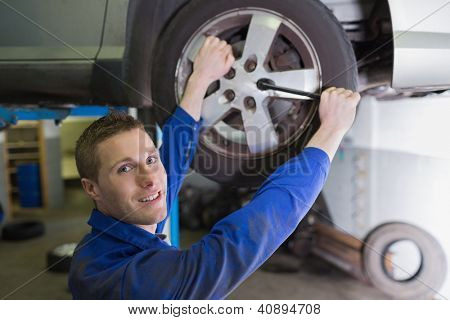 Portrait of confident male mechanic changing car tire