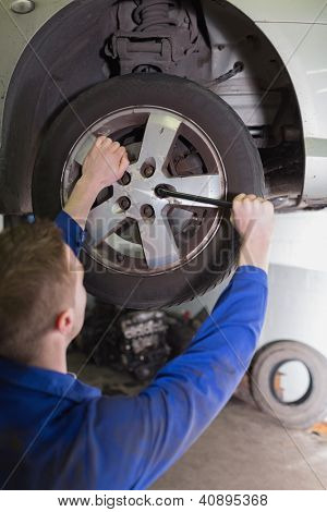 Male mechanic fixing car wheel in workshop