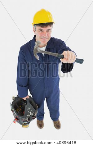 High angle view of mature mechanic with hammer carring tool bag against white background