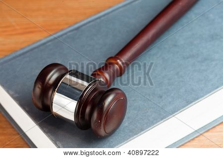 Gavel resting on a blue book on desk