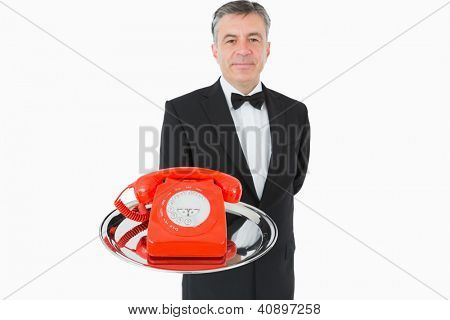 Waiter holding red phone on silver tray
