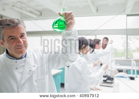 Chemist happily hold ing beaker of green liquid in bus ylab