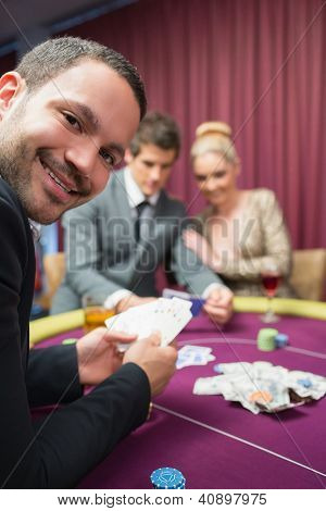 Man smiling while sitting at poker table in casino