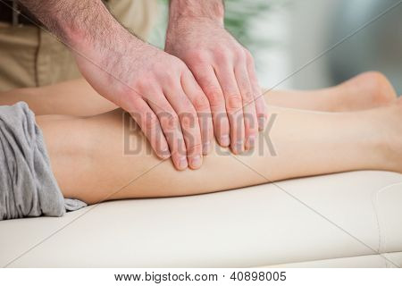 Woman lying forward while a man massaging her calf indoors