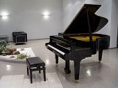 foto of grand piano  - Concert grand piano in illuminated theatrical foyer.