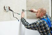 pic of electrician  - Young electrician at work with wall outlet and screwdriver installing sockets - JPG