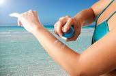 stock photo of sunburn  - Woman applying sunscreen on her arm on a beach - JPG