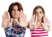 stock photo of racial discrimination  - Young latin woman and a teenage girl signaling to stop with their hands extended isolated on white  - JPG