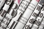 stock photo of newspaper  - Newspaper headlines shown side on in a stack of daily newspapers - JPG