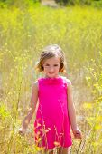 child kid girl in spring yellow flowers field and pink dress in Mediterranean forest