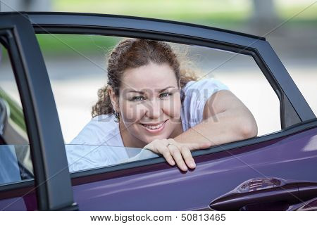 Young Joyous Beauty Woman Looking At Opened Car Window In Door