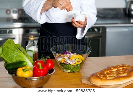 Chef Sprinkling Salt On Vegetables
