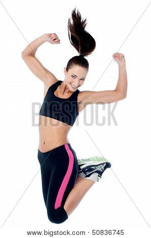 Young Girl In Sportswear Jumping With Joy