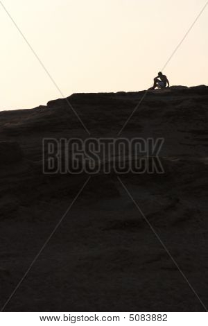Silhouette Of A Man Sitting On A Dune