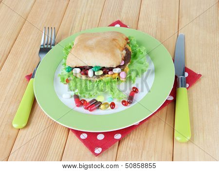 Conceptual image for nutritional care:assorted vitamins and nutritional supplements in bun. On wooden background