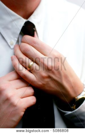 Married Hands Straighten A Tie