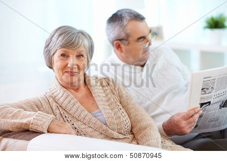 Portrait of mature woman looking at camera on background of her husband reading newspaper