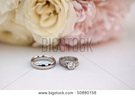 wedding rings in front of bouquet of pink roses