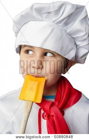 Isolated little boy cook in uniform over vintage  background playing with spoon