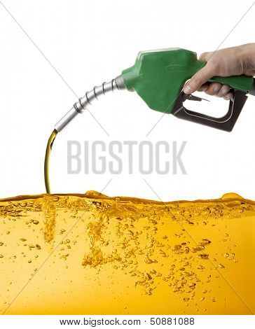 Hand holding a nozzle pumping gasoline in a tank