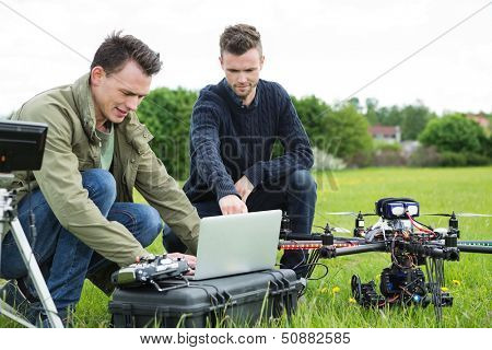 Young technicians using laptop by UAV drone in park
