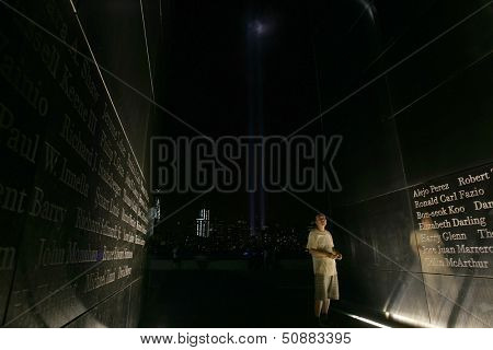 JERSEY CITY, NJ - SEPTEMBER 11: An unidentified man stands within the Empty Sky 9/11 Memorial on September 11, 2013 in Jersey City, NJ. The Tribute in Light installation is visible in the background.