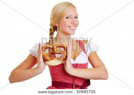 Happy Bavarian woman in a dirndl holding a pretzel