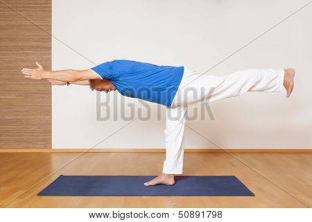 An image of a man doing yoga exercises - Virabhadrasana