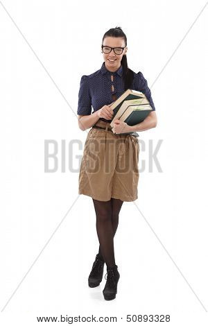 Pretty young school-marm standing legs crossed, smiling with books in hands.