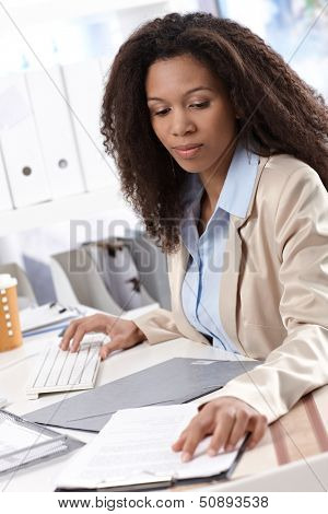 Young ethnic businesswoman sitting at desk, working on computer.