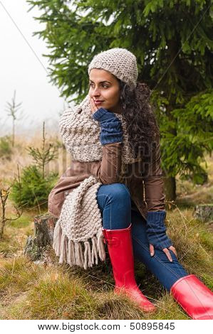 Woman sitting on ground autumn foggy pinewood in knitted scarf
