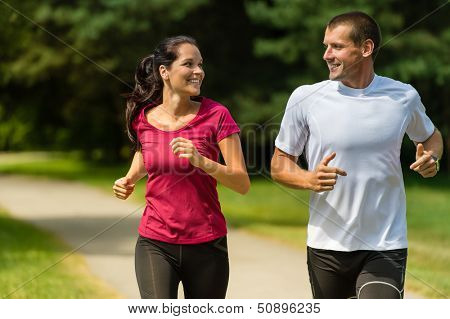 Portrait of cheerful Caucasian couple running outdoors