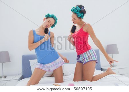 Girls in hair rollers singing with hairbrush in bed at sleepover