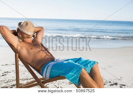 Handsome man on the beach sleeping on his deck chair