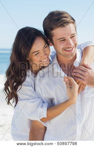 Smiling couple embracing each other on the beach against ocean on a sunny day