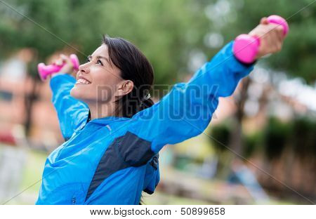 Happy woman exercising with arms up and free-weights