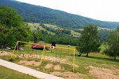 foto of oddities  - adult man swinging on swing over rural landscape - JPG