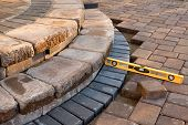 stock photo of trowel  - Pavers meets with patio steps and job completion almost done last check with yellow level - JPG