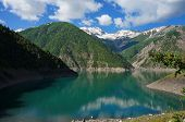 foto of swales  - Charming lake among high picturesque mountains and a cloud in the blue sky in Kyrgyzstan - JPG